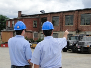 hard hat men pointing to factory